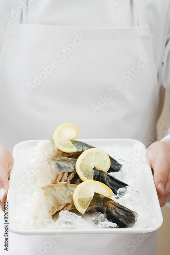 person holding tray of king prawns on ice