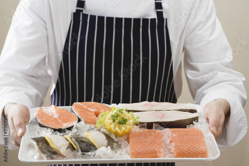 person holding tray of salmon and sea bass pieces on ice