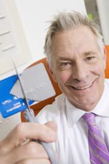 Businessman Cutting Credit Card