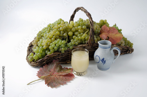 green grapes in basket, grape must and leaves