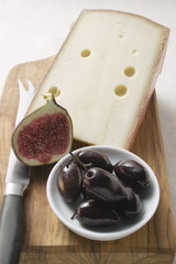 piece of hard cheese, half a fig and olives