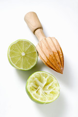 two lime halves, one squeezed, with lemon squeezer