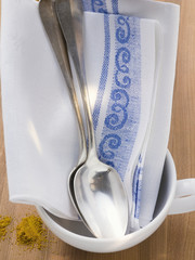 tea towel and two spoons in white cup