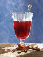 a glass of jagertee with sugar crystals, cinnamon & cloves