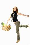 young woman holding shopping basket full of fresh food