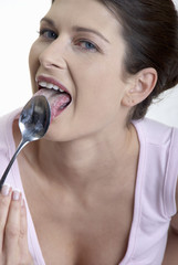 woman licking yoghurt from a spoon
