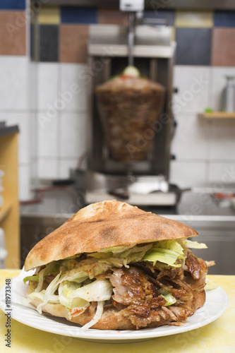 a döner kebab with meat on spit in background