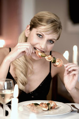 young woman biting into a shrimp kebab