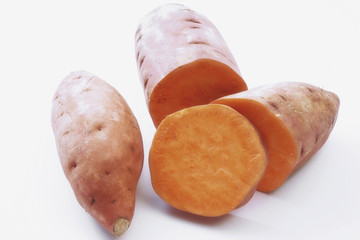 two sweet potatoes, one partly sliced