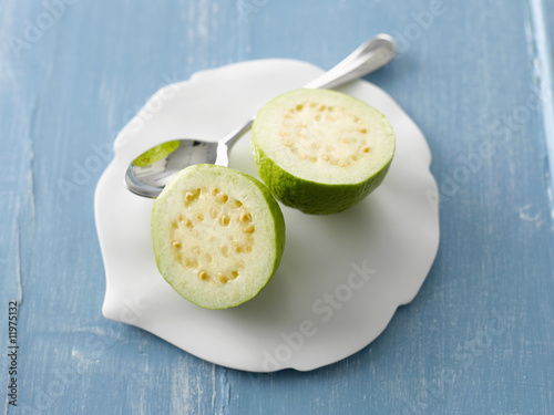 halved guava with spoon on china plate