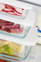 cheese, salami & radishes in food storage boxes in fridge
