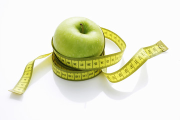a green apple with a tape measure