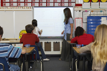Female Teacher standing  by whiteboard and assisting schoolgirl