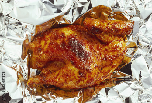 half a grilled chicken on aluminium foil
