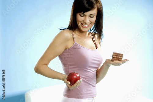young woman holding piece of cake and apple in her hand