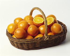 fresh oranges in a shallow wicker basket