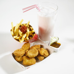chicken nuggets, chips, sauce and milkshake