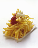 french fries on a paper plate with ketchup and mayonnaise