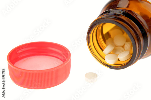 Pills in jar on white