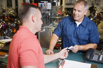 Customer in Motorcycle Shop Paying