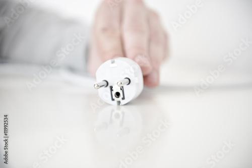 hand von mann zieht stromstecker