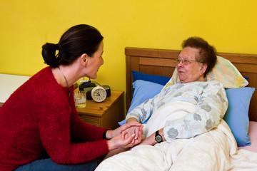 Kranke alte Frau wird von Tochter besucht