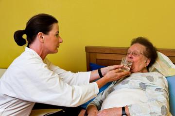 Pfleger betreut alte Frau im Altersheim