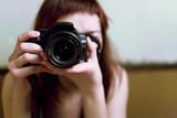 Jeune femme prenant une photo avec un reflex numérique en mains poster
