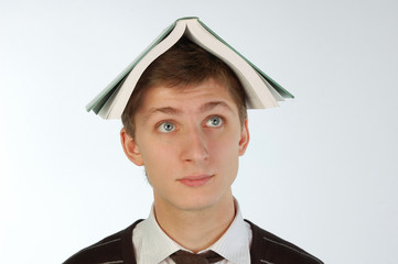 Young man with a book on his head