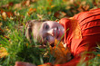 little girl laying on autumn leaves and smiling