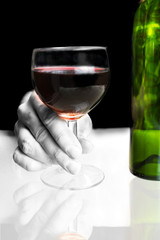 Hand holding red wine glass with bottle