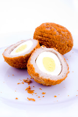 A halved scotch egg on plate on white