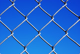 Chain Link Fence Up Close Against a Vivid Sky