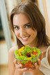 Portrait of young woman with salad at home