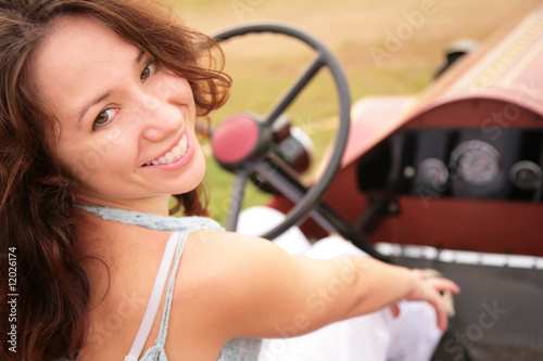 Woman sits having turned back in salon of the ancient car