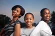 Three beautiful smiling teenage African American girls outdoors