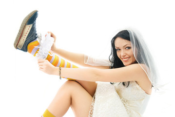 bride wearing sporting shoes puts on a garter