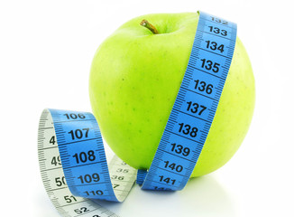 Bright green apple and measuring tape isolated