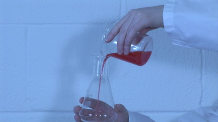 Scientist decanting a red liquid
