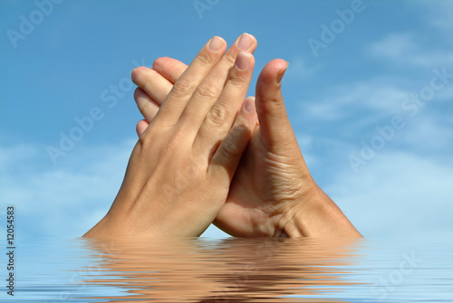 Hands in hands on water against sky