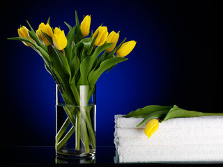 Towels near to a bouquet from yellow tulips.