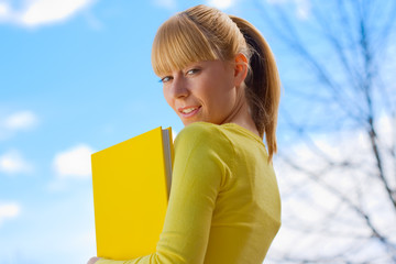 Beautiful blond girl with yelow book
