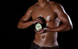 A hunky asian man holding a clock in his hands,