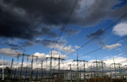 Electricity poles and wires against dramatic blue cloudy sky - 12071771