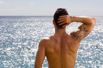 Chico de espaldas mirando hacia el mar