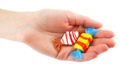 Woman's hand gives two colored candy