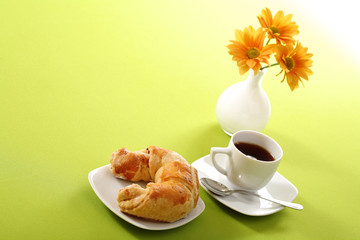 Breakfast concept with coffee and croissant