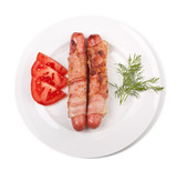 sausages wrapped in bacon served with sliced tomatoes