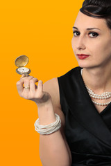 stylish lady holding classic golden watch and looking at camera