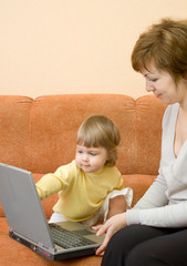 Mother with daughter on sofa with laptop
